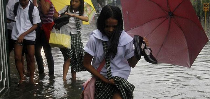 Students in knee-deep floodwater in Quezon City after a heavy downpour